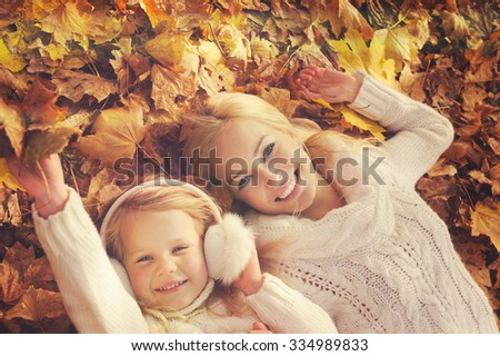 Happy smiling caucasian blonde mother and daughter dressed in white knitted sweaters, lying in yellow autumn foliage, top view, leisure in autumn park. - stock photo