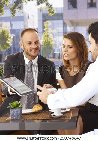 Happy smiling caucasian businessman sharing online news on tablet computer at outdoor internet cafe. Suit and tie. - stock photo