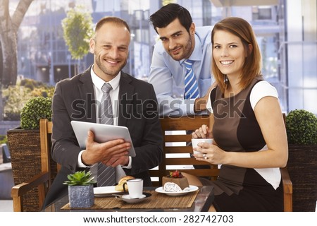 Happy, smiling caucasian businesswoman and businessmen enjoying success at breakfast, Suit and tie, tablet computer, looking at camera, outdoor. - stock photo