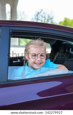 Happy smiling Caucasian child looking at window of car - stock photo