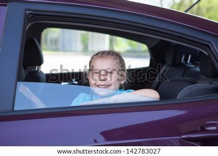 Happy smiling Caucasian child sitting in land vehicle on back seat - stock photo