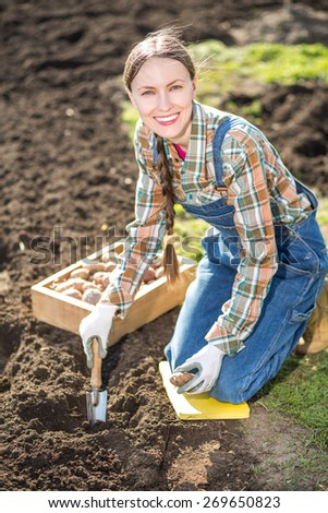 Happy smiling caucasian female farmer or gardener holding potato going to plant. Agriculture - food production, home grown food concept - stock photo