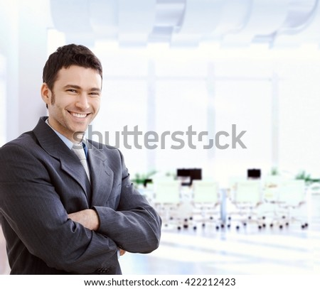 Happy smiling caucasian financial business expert standing at office lobby, arms crossed, looking at camera, copyspace, suit. - stock photo