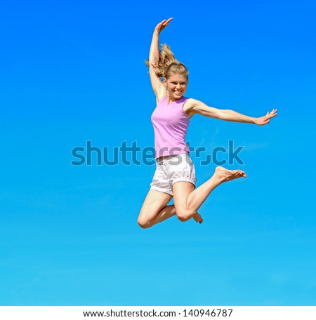 Happy smiling Caucasian woman jumping over sky background. - stock photo