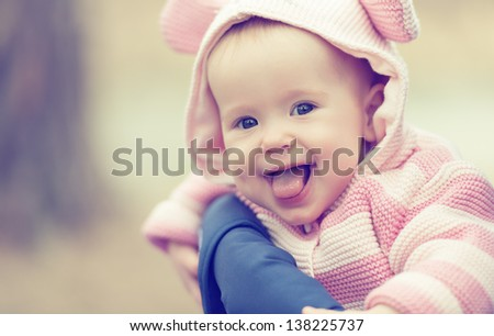 happy smiling cheerful baby girl in pink hood with ears - stock photo