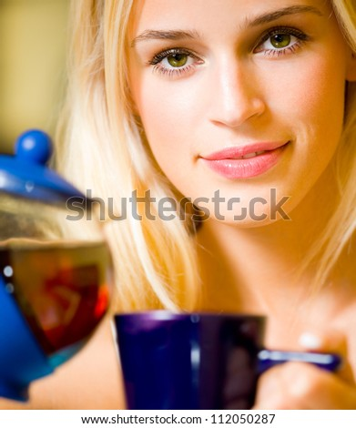Happy smiling cheerful blond girl with teapot and cup, at home - stock photo