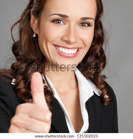 Happy smiling cheerful young business woman showing thumbs up gesture, over grey background - stock photo