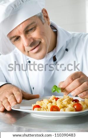 Happy smiling chef garnish an Italian pasta dish with basil leaves - stock photo