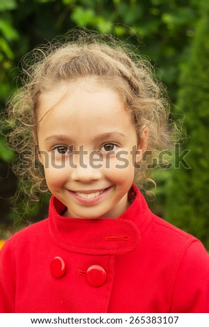 Happy smiling child in red jacket outside - stock photo