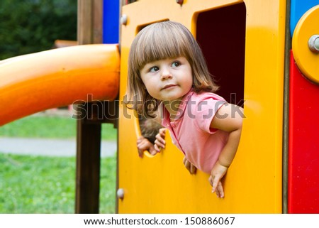 Happy smiling child   in small house on playground  - stock photo