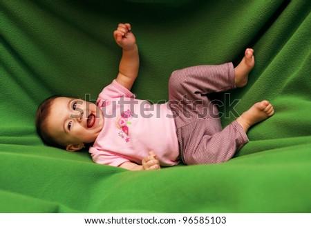Happy smiling child on green blanket - stock photo