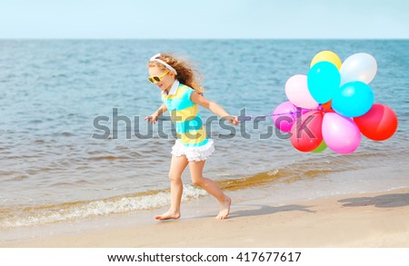 Happy smiling child playing on beach running with colorful balloons over sea  - stock photo