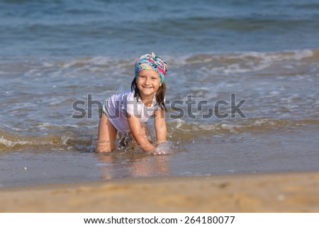 Happy smiling child playing on the beach at the water's edge. Shallow depth of field. Focus on the model. - stock photo
