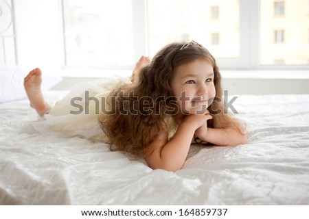 Happy smiling child waking up in the morning. Dream the little princess on a white bed close-up. - stock photo