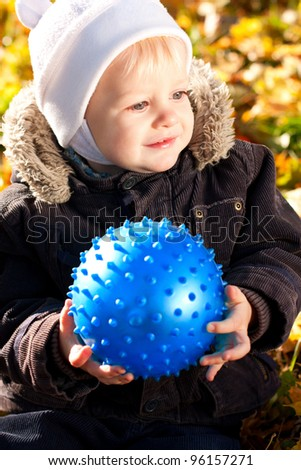 Happy smiling child with blue ball in his hands against a background of autumn sunny nature - stock photo