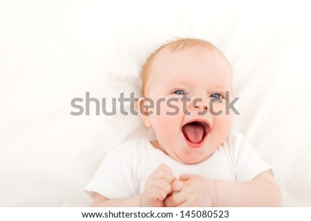 happy smiling child with blue eyes lying in bed over white - stock photo
