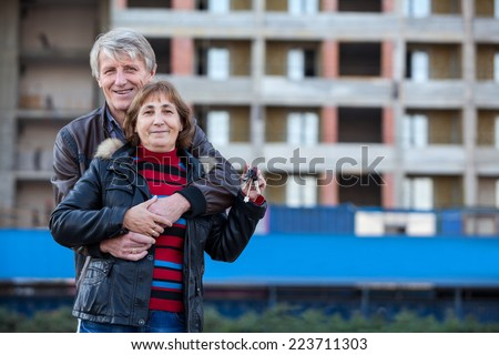 Happy smiling couple embracing outdoor with house key in hand, copyspace - stock photo