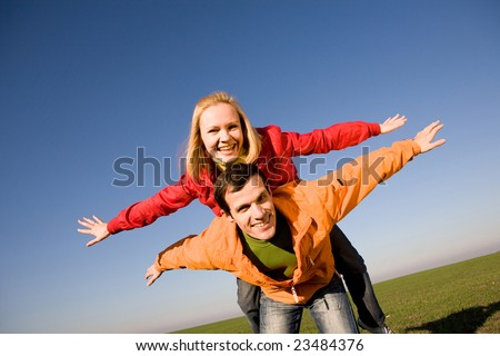 Happy smiling couple fly in sky - stock photo