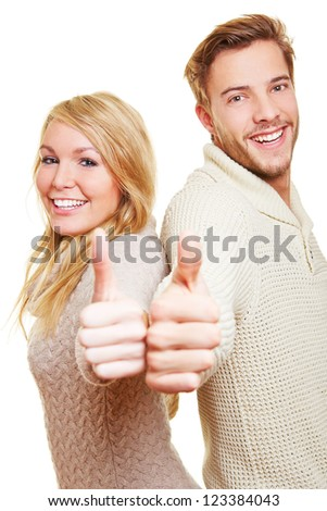 Happy smiling couple holding their thumbs up together - stock photo