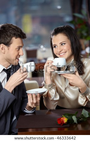 Happy smiling couple in cafe with cups in hands - stock photo