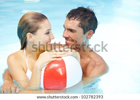 Happy smiling couple in swimming pool with beach ball - stock photo
