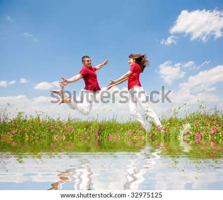 Happy smiling couple  jumping in sky above a green meadow . Reflected in Water. - stock photo