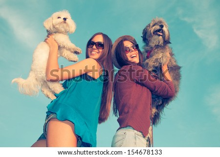 happy smiling couple of girlfriends hold up their dogs outdoor shot with blue sky in background  retro colors - stock photo