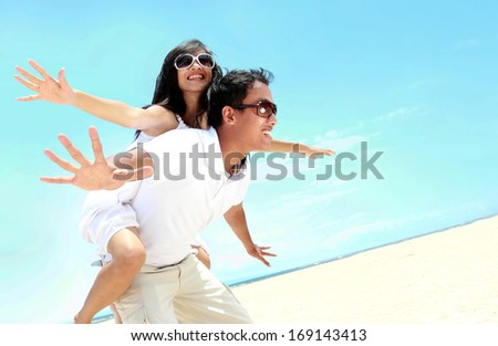 Happy smiling couple piggyback together with arms outstretched at beautiful beach - stock photo