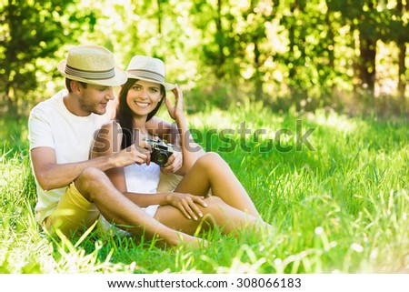 Happy smiling couple relaxing on green grass. Summer day - stock photo