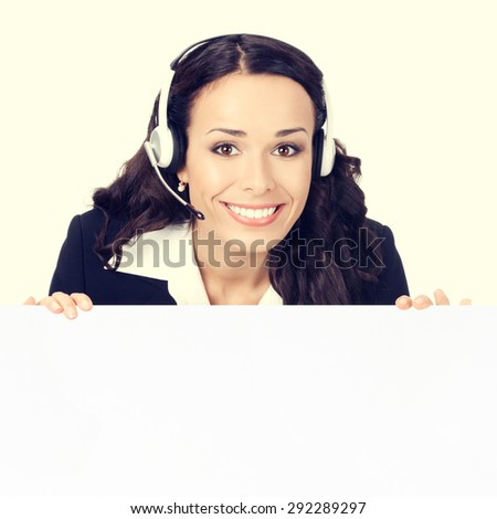 Happy smiling customer support phone operator or businesswoman in headset showing blank signboard - stock photo