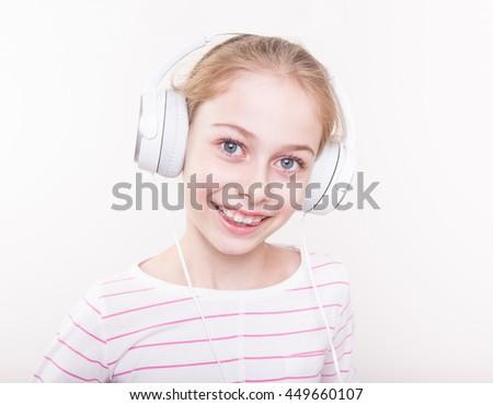 Happy smiling eight years old pretty blond caucasian child girl listening music in white headphones. - stock photo
