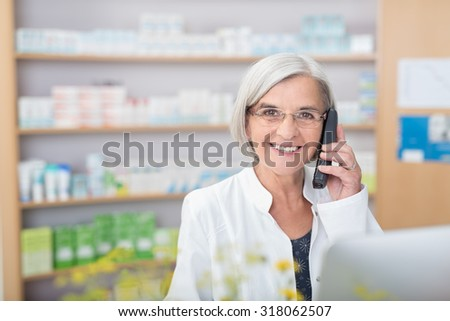 Happy smiling elderly female pharmacist talking on a telephone as she stands behind the counter in the pharmacy assisting a client - stock photo