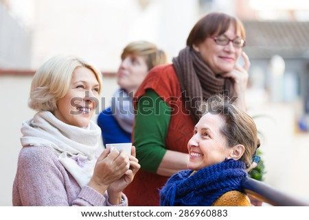 Happy smiling elderly females drinking coffee at patio. Focus on brunette - stock photo