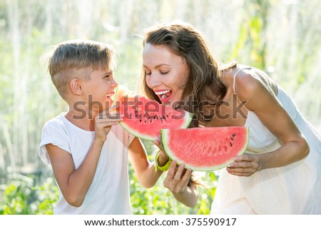 Happy smiling family eating watermelon on a sunny summer day - stock photo
