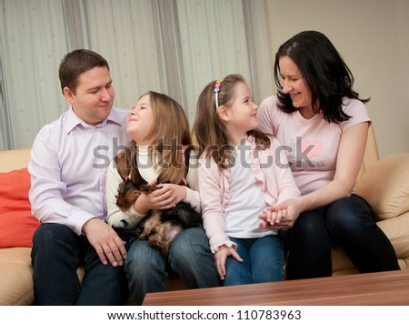 Happy smiling family enjoying together at home and dog - stock photo