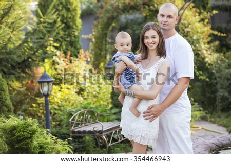 Happy smiling family of slim fit beautiful brunette mother, bold fat father and cute little infant baby in a green park in blue and white outfit: t-shirt, shorts and dress. Summer. Copy space - stock photo