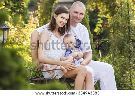 Happy smiling family of slim fit beautiful brunette mother, bold fat father and cute little infant baby in a green park in blue and white outfit: t-shirt, shorts and dress. Summer - stock photo