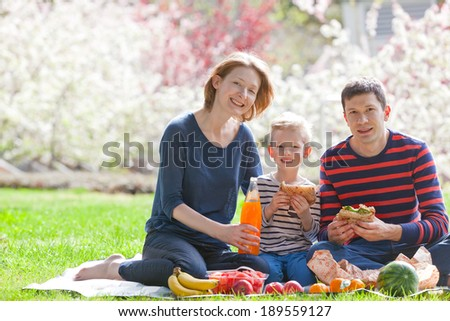 happy smiling family of three having a picnic outside together, eating sandwiches and fruits - stock photo