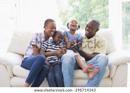 Happy smiling family on the couch in the living room - stock photo