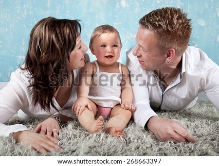 Happy Smiling Family Portrait. Father and Mother with Little Baby - Laughing. Parents with Child  - stock photo