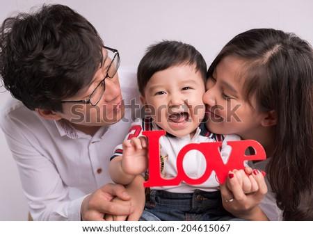 "Happy Smiling Family Portrait isolated on White Background. Baby boy holding ""LOVE"" symbol - stock photo"
