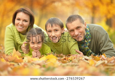 Happy smiling family relaxing in autumn park - stock photo