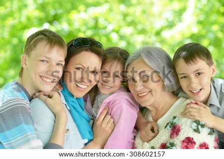 Happy smiling family relaxing in summer park - stock photo