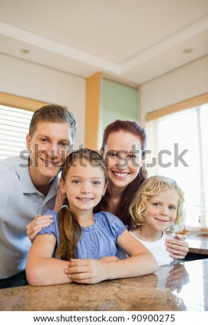 Happy smiling family standing behind the kitchen counter - stock photo