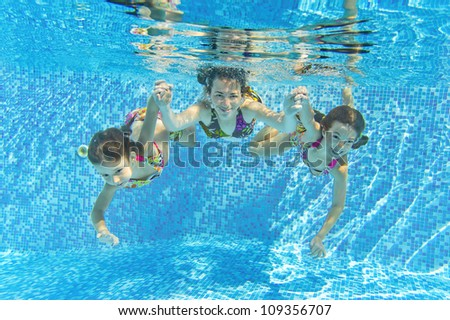 Happy smiling family underwater in swimming pool. Mother and children swim and having fun. Kids sport on family summer vacation. Active healthy holiday - stock photo