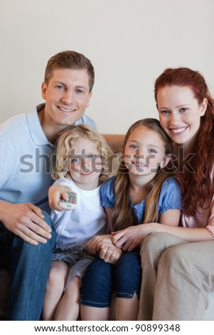 Happy smiling family watching television together - stock photo