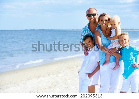 Happy smiling family with children standing on the sunny beach. - stock photo