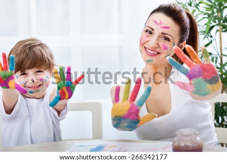Happy smiling family with colored hands enjoy at home - stock photo