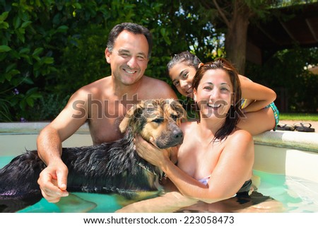 Happy smiling family with dog having fun together in the swimming pool. - stock photo