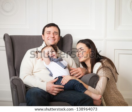 Happy smiling family with one year old baby girl indoor - stock photo